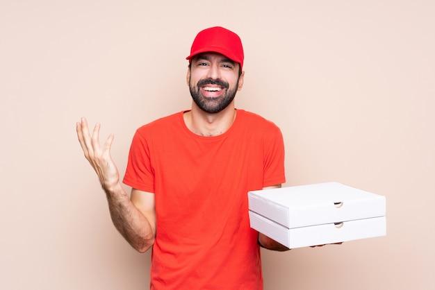 多くの笑みを浮かべて孤立した背景の上にピザを置く若い男