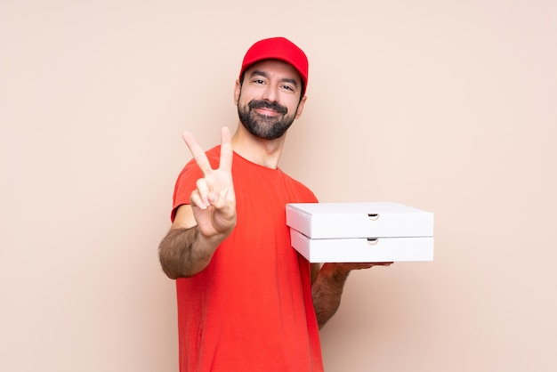 笑みを浮かべて、勝利のサインを示す孤立した背景にピザをかざす若い男