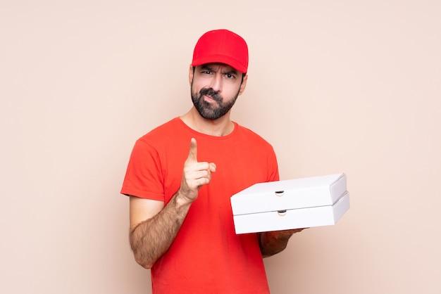 イライラし、前方を向く孤立した背景の上にピザを保持している若い男