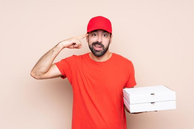 若い男が頭に指を置いて狂気のジェスチャーを作る孤立した背景にピザを保持
