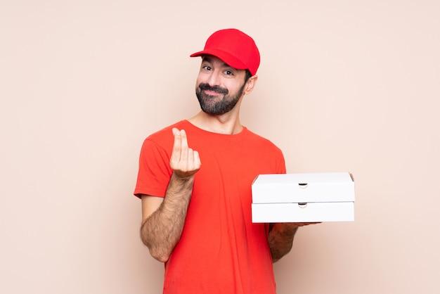 お金のジェスチャーを作る分離の背景の上にピザを置く若い男