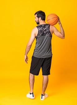 孤立した黄色の背景の上にバスケットボールをプレーする男の全身ショット