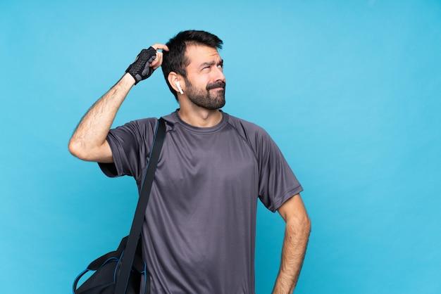 頭をかきながら疑問を持つ分離の青い壁の上のひげを持つ若いスポーツ男