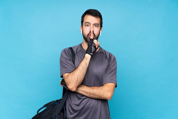 Молодой спортивный человек с бородой над изолированной синей стеной, показывая знак жеста молчания, положив палец в рот