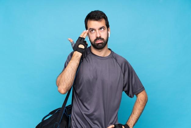 自殺ジェスチャーを作る問題と分離の青い壁の上のひげを持つ若いスポーツ男