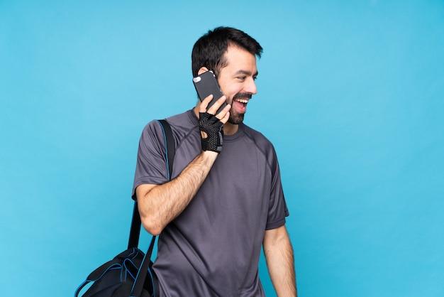 携帯電話との会話を維持する分離の青い壁の上のひげを持つ若いスポーツ男