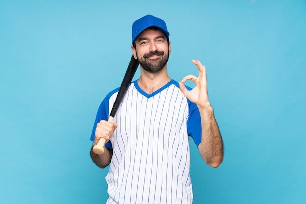 Молодой человек играет в бейсбол над синей стеной, показывая хорошо знаком с пальцами