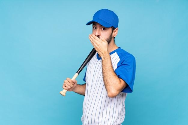 Молодой человек играет в бейсбол над изолированным синим ртом для покрытия стен руками