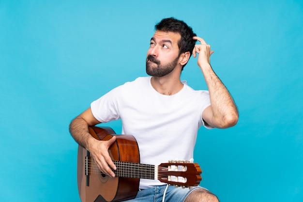 頭をかきながら疑問を持つ分離の青い壁の上のギターを持つ若い男