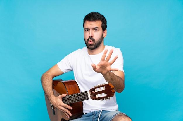 Молодой человек с гитарой над изолированной синей стеной нервно протягивая руки к фронту
