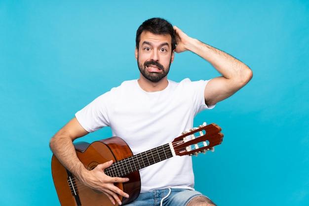 孤立した青い壁の上のギターを持つ若い男がイライラし、頭の上の手を取る