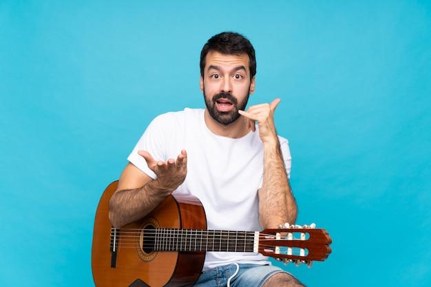 電話ジェスチャーを作ると疑う分離の青い壁の上のギターを持つ若い男