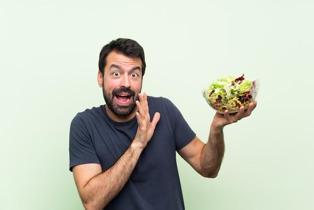 Молодой красавец с салатом на изолированных зеленая стена нервной и страшно