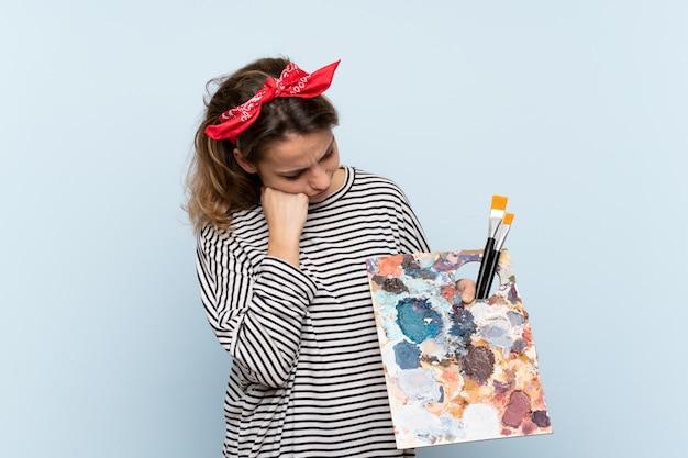 悲しそうな表情で孤立した青い壁にパレットを保持している若いアーティストの女性