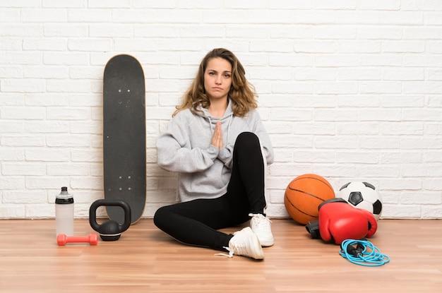 Молодая спортивная женщина сидит на полу, умоляя