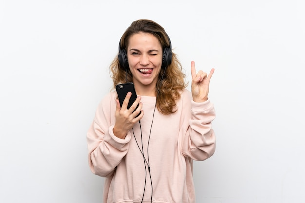 Молодая блондинка с помощью мобильного телефона с наушниками и пения