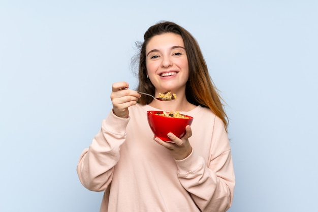 Молодая брюнетка девушка над синей стеной, держа миску каши