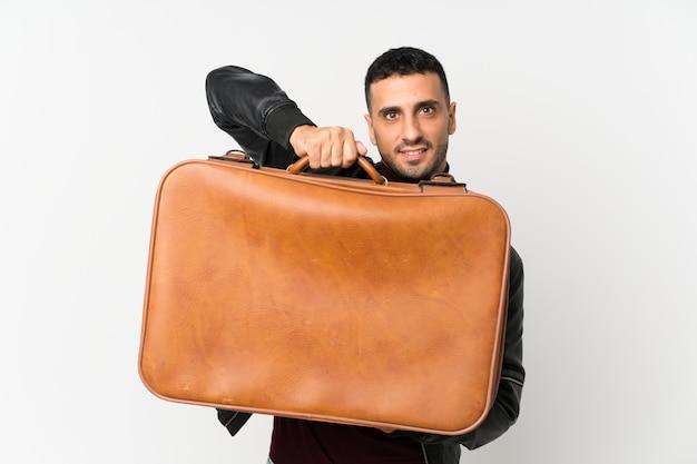 Молодой человек над изолированной белой стеной держит винтажный портфель