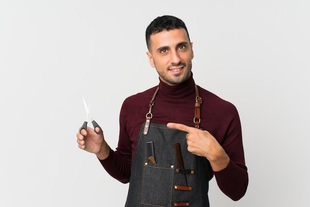 Молодой человек над изолированной белой стеной с платьем парикмахера или парикмахера и указывать его