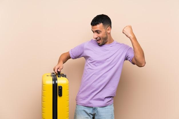 Мужчина держит чемодан над изолированной стеной, празднует победу