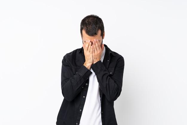 疲れや病気の表情で孤立した白い壁の上のひげを持つ若者