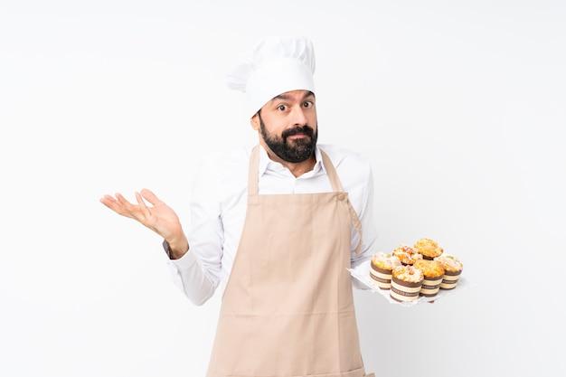 疑問ジェスチャーを作る分離の白い壁にマフィンケーキを置く若い男