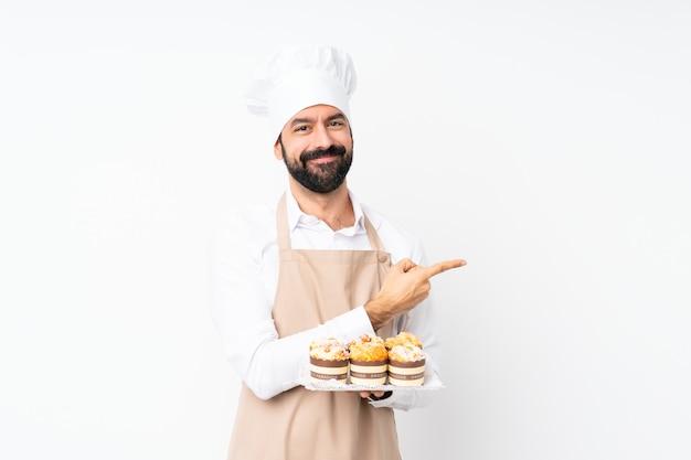 製品を提示する側を指している孤立した白い壁にマフィンケーキを置く若い男