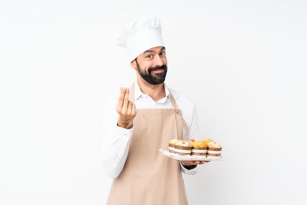 お金のジェスチャーを作る分離の白い壁にマフィンケーキを置く若い男