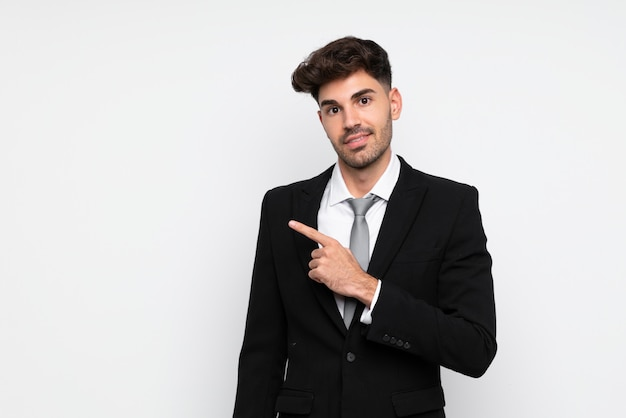 Молодой предприниматель на белом фоне, указывая пальцем в сторону