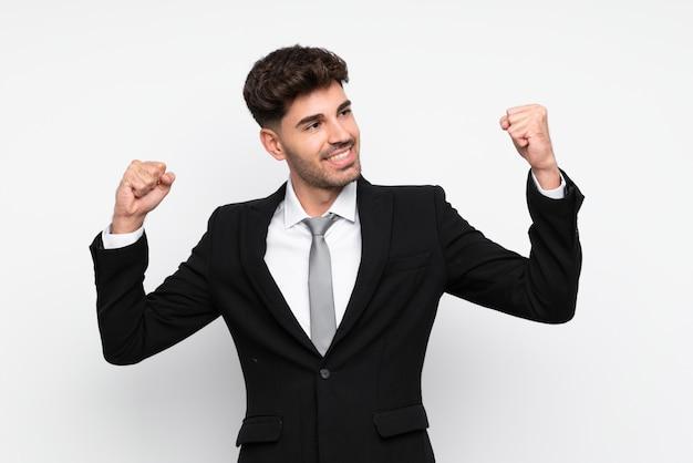 Молодой бизнесмен над изолированной белой стеной празднуя победу