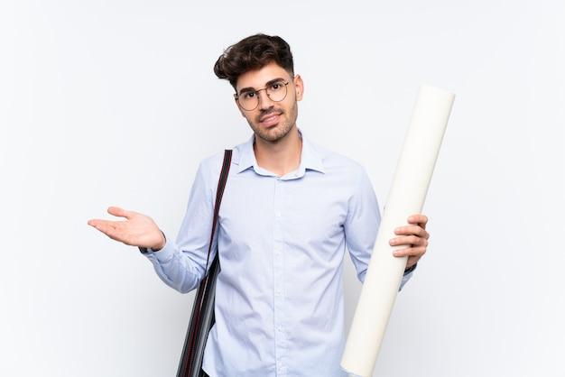 Молодой архитектор человек над белой стене, протягивая руки в сторону за приглашение прийти