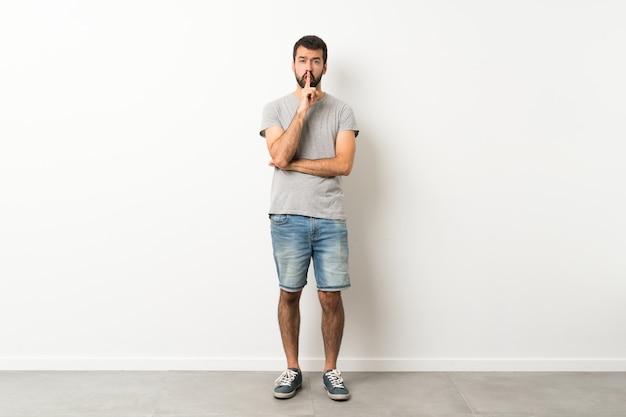 Полнометражный снимок красивого мужчины с бородой, показывающего знак жеста молчания, кладущего палец в рот