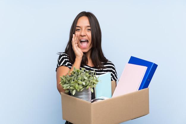 Молодая брюнетка делает ход, собирая коробку с вещами, кричащими с широко открытым ртом