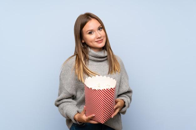 ポップコーンのボウルを保持している孤立した青い背景上のセーターとティーンエイジャーの女の子