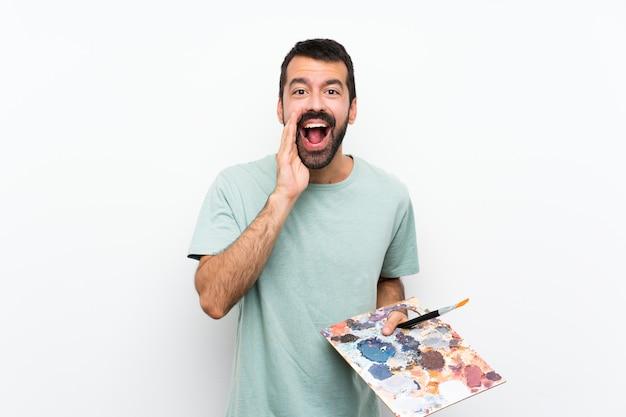 叫び、何かを発表分離の背景の上にパレットを保持している若いアーティスト男