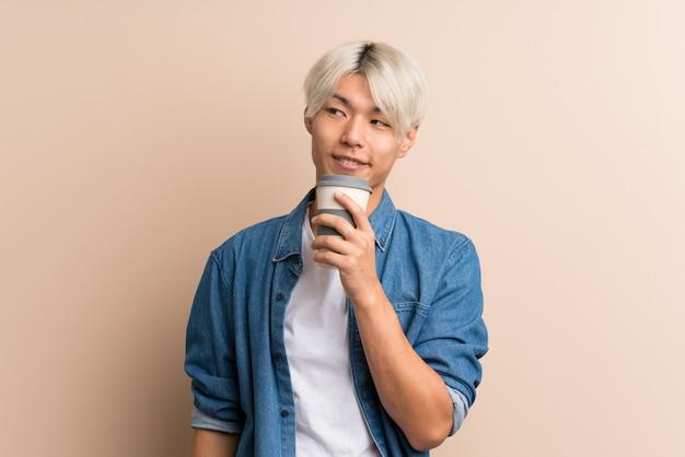 奪うためにコーヒーを保持している若いアジア人