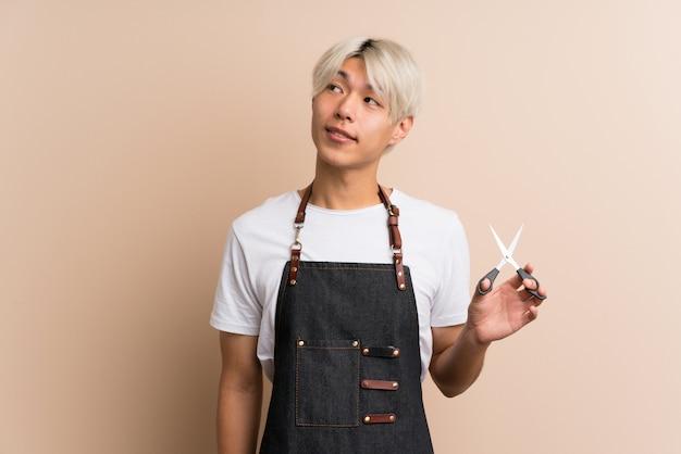 見上げる美容師や理髪店のドレスの若いアジア人