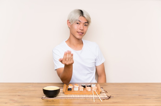 来て招待してテーブルに寿司を持つ若いアジア人