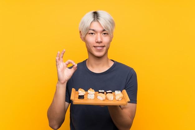 Молодой азиатский человек с сушами над изолированным желтым цветом показывая одобренный знак с пальцами
