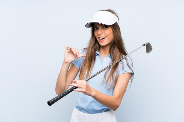 誇りに思って、自己満足の孤立した青い壁の上の若いゴルファーの女性
