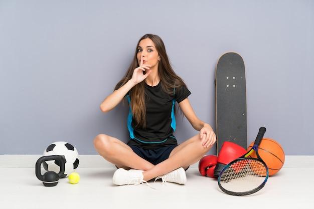 Молодая спортивная женщина сидит на полу, делая жест молчания