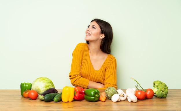 Девушка подростка с много овощей счастливая и усмехаясь