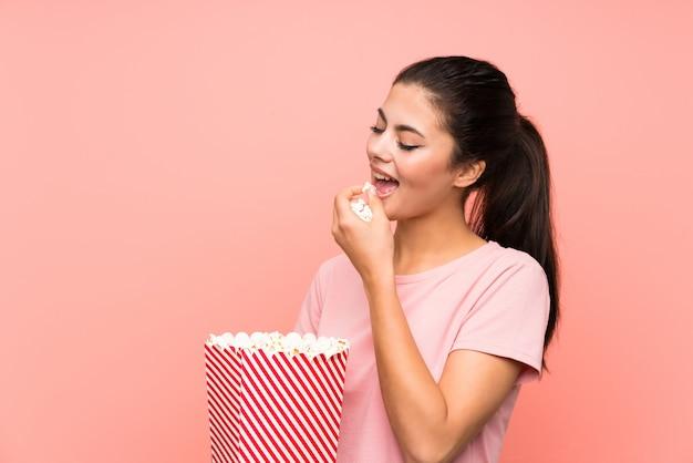 ポップコーンを食べて孤立したピンクの壁の上のティーンエイジャーの女の子