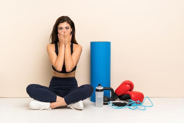 緊張と怖がって手を口に入れて床に座ってティーンエイジャーのスポーツ少女