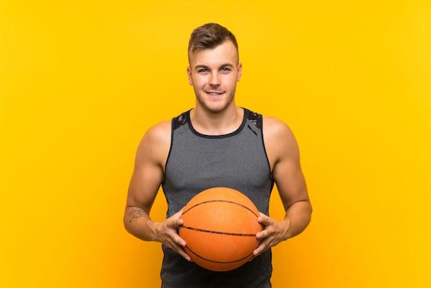 孤立した黄色の背景にバスケットボールを保持している幸せな若いハンサムな金髪男