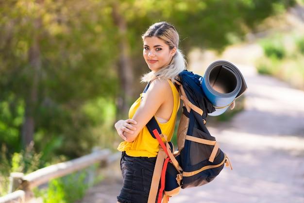 腕を組んで、楽しみにして屋外でハイキングのティーンエイジャーの女の子