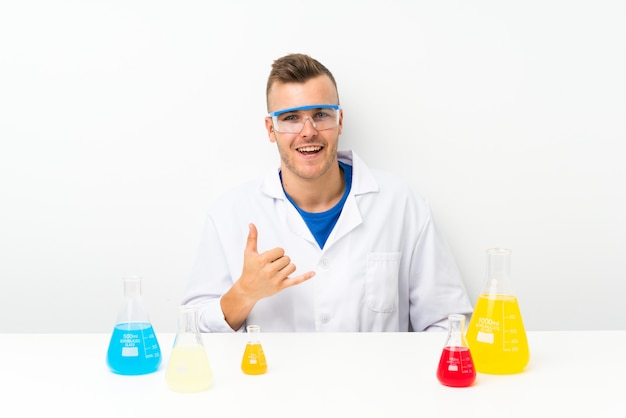 Молодой ученый с большим количеством лабораторных колб, делая жест телефона