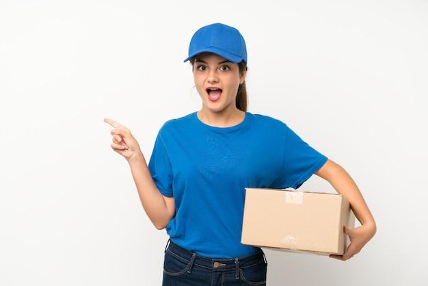 Молодая девушка доставки над изолированной белой удивлен и указывая пальцем в сторону
