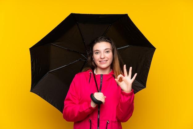 Молодая девушка брюнет держа зонтик над изолированным желтым цветом показывая одобренный знак с пальцами