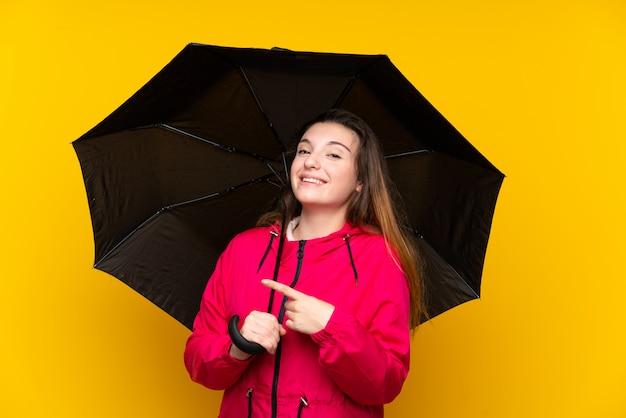 分離された黄色に傘をかざす若いブルネットの少女は驚いて、側を指して